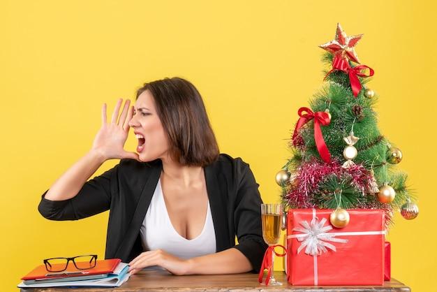 젊은 아름다운 여자가 누군가를 호출하고 사무실에 앉아있는 크리스마스 분위기