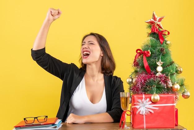 자랑스럽게 그녀의 성공을 즐기는 젊은 비즈니스 아가씨와 함께 크리스마스 분위기