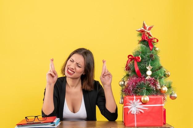 Рождественское настроение с молодой концентрированной красивой женщиной, сидящей в офисе