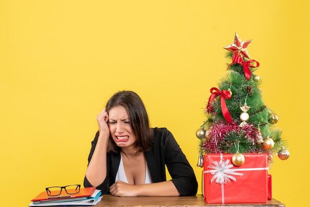 젊은 감정적 인 아름다운 여자와 크리스마스 분위기는 신중하게 사무실에 앉아있는 것에 집중했습니다.