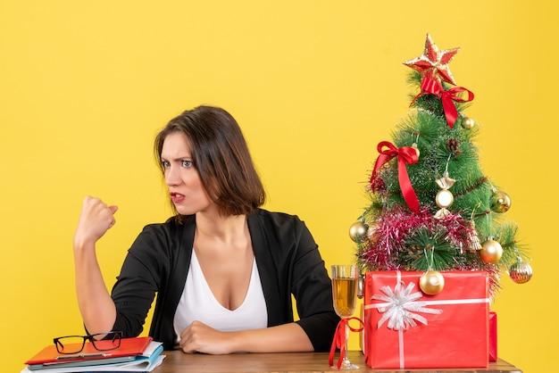 Umore di natale con la giovane signora di affari tesa stressata emotiva seduta a un tavolo in ufficio