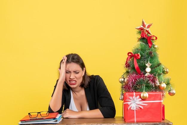 젊은 정서적 긴장된 아름다운 여자와 크리스마스 분위기는 신중하게 사무실에 앉아 뭔가에 집중