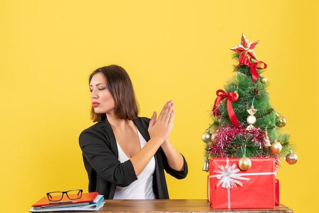Umore di natale con la giovane bella donna felice che esamina qualcosa all'ufficio