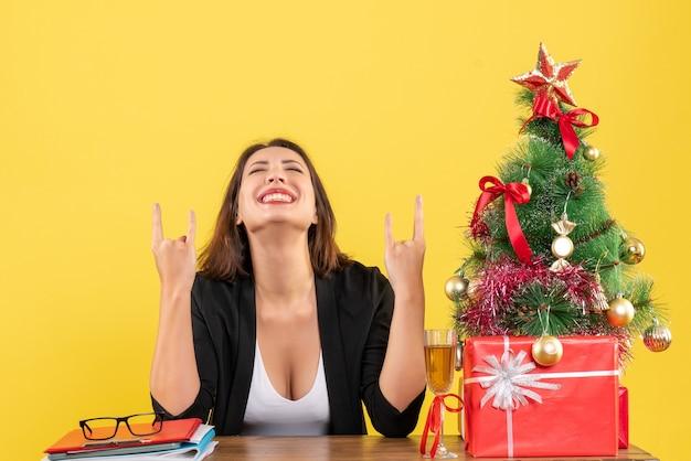 그녀의 성공을 즐기고 사무실에 앉아 젊은 행복 비즈니스 아가씨와 함께 크리스마스 분위기