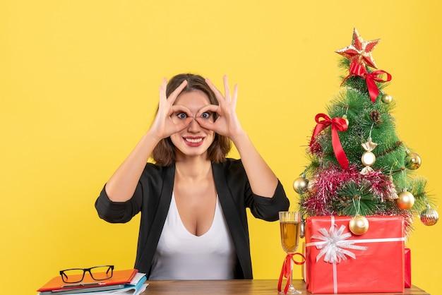 노란색에 그녀의 두 손으로 화려한 제스처를 만드는 젊은 행복 비즈니스 아가씨와 함께 크리스마스 분위기