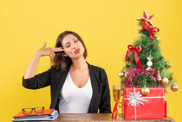 그녀의 눈을 감고 노란색에 사무실에서 테이블에 앉아 뭔가에 대해 꿈을 꾸고 젊은 행복 감정적 인 비즈니스 아가씨와 함께 크리스마스 분위기