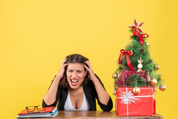 노란색에 사무실에 신중하게 앉아 뭔가에 초점을 맞춘 젊은 긴장 감정적 인 아름다운 여자와 크리스마스 분위기