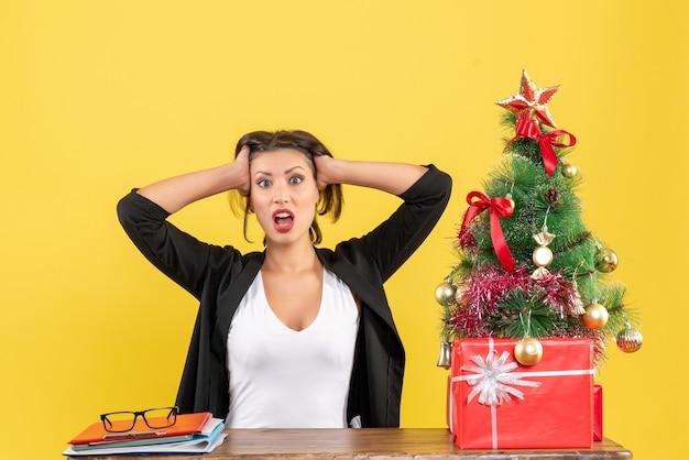 노란색에 사무실에 앉아 젊은 긴장 감정적 인 아름다운 여자와 크리스마스 분위기