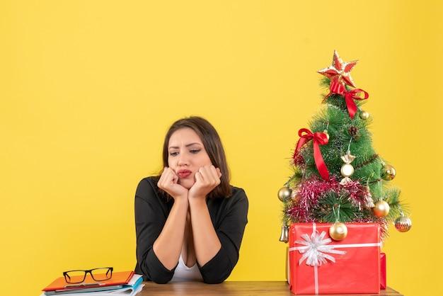 노란색에 사무실에 신중하게 앉아 뭔가에 초점을 맞춘 젊은 심각한 아름다운 여자와 크리스마스 분위기