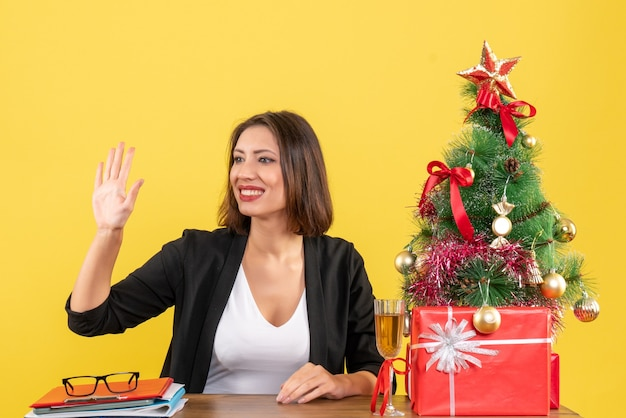 Umore di natale con la giovane signora sorridente di affari che dice addio felicemente sul giallo