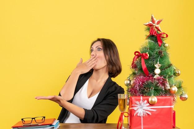 노란색에 사무실에서 테이블에 앉아 젊은 놀란 감정 비즈니스 아가씨와 함께 크리스마스 분위기