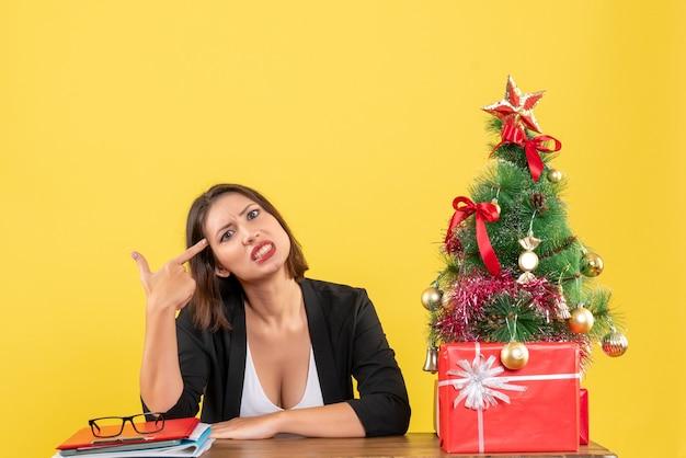 노란색에 사무실에서 뭔가를보고 젊은 긴장된 아름다운 여자와 크리스마스 분위기