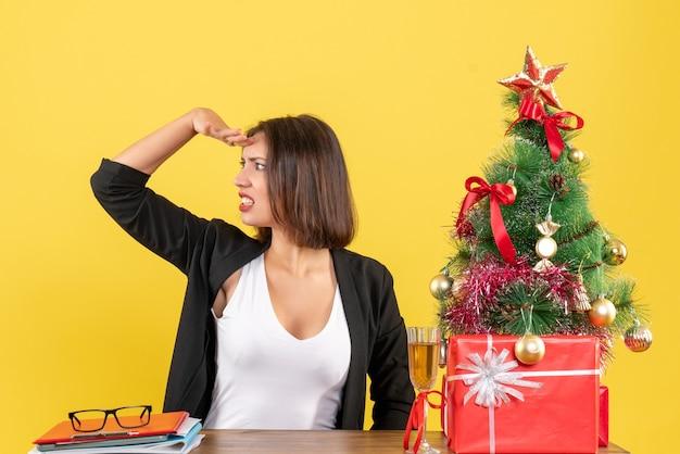 黄色で何かを注意深く見ている若い不満の深刻な感情的なビジネスの女性とのxsmas気分
