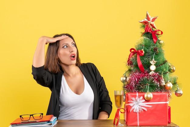 黄色で意外と見上げる若い不満の深刻な感情的なビジネスの女性とxsmas気分