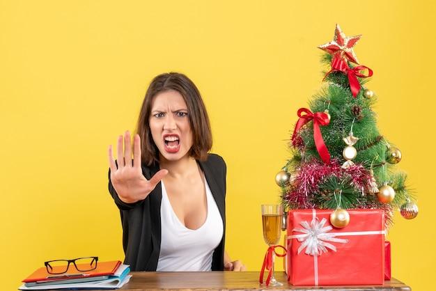 Umore di natale con la giovane signora di affari emotiva seria insoddisfatta che mostra il gesto di arresto sul giallo