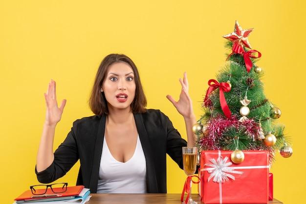 黄色に現れる若い不満の深刻な感情的なビジネスの女性とxsmas気分