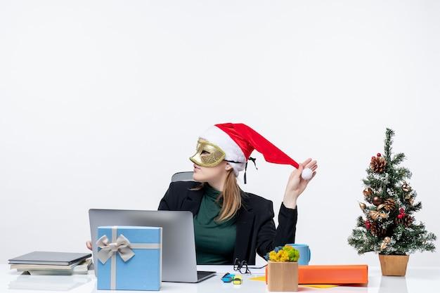 Atmosfera natalizia con la giovane donna che gioca con il cappello di babbo natale e indossa la maschera seduto a un tavolo su sfondo bianco
