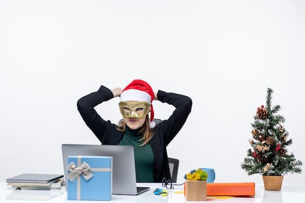 Рождественское настроение с молодой женщиной в шляпе санта-клауса и в маске, сидящей за столом на белом фоне