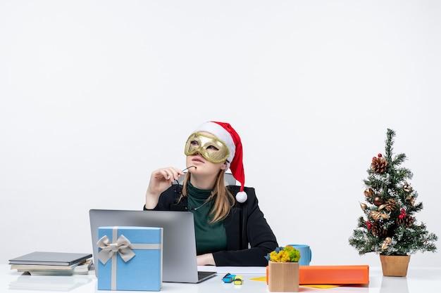 Umore di natale con la giovane donna con il cappello di babbo natale che tiene gli occhiali e che indossa la maschera seduti a un tavolo e in pensieri profondi su sfondo bianco