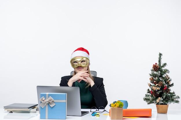 Atmosfera natalizia con giovane donna con cappello di babbo natale e maschera da portare seduto a un tavolo ascoltando attentamente qualcuno su sfondo bianco