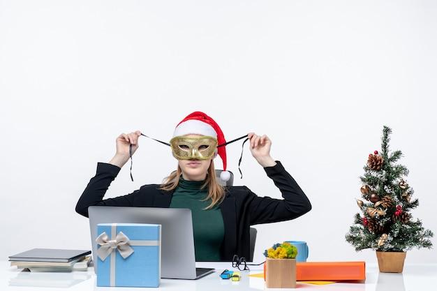 Atmosfera natalizia con giovane donna con cappello di babbo natale e maschera da portare seduto a un tavolo sul metraggio di sfondo bianco