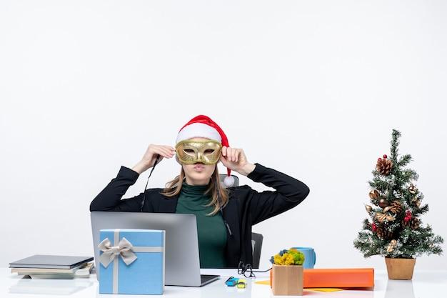 Atmosfera natalizia con giovane donna con cappello di babbo natale e maschera da portare seduto a un tavolo su sfondo bianco stock photo