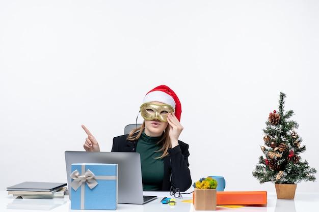Atmosfera natalizia con giovane donna con cappello di babbo natale e maschera da portare seduto a un tavolo su sfondo bianco