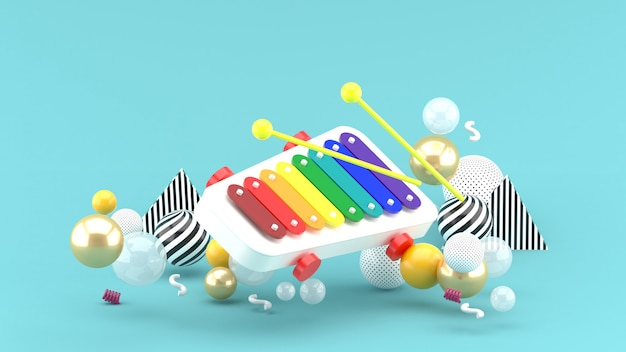 Xylophone toy among colorful balls on blue space