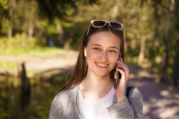 Y a young beautiful girl with sunglasses walks and talks on the phone on a sunny spring day