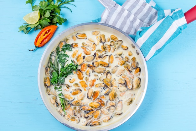 ムール貝のミルククリームyソースの香り高いハーブとレモンの赤鍋料理。青い背景