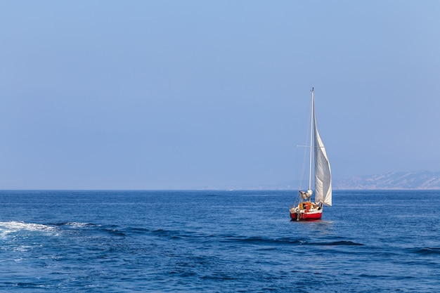 Яхта плывет по морю красный парусник отдых отдых активный образ жизни