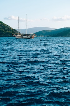 The yacht glides on blue water against the backdrop of mountains off the coast of the city of perast
