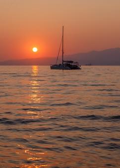 日没のオレンジ色の海のヨット背景の山々落ち着きと静けさギリシャ