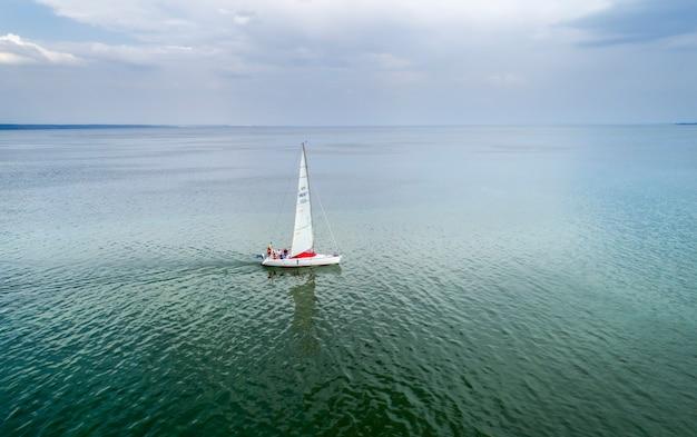 ヨットレース、空撮。夏の曇りの日に外洋でヨットに乗っている乗客。帆船でのクルーズの映画のような風景。
