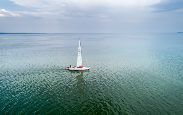 Yacht racing, aerial view. passengers on sailboat at open sea at summer cloudy day.  cinematic scenery of cruise on sail boat.