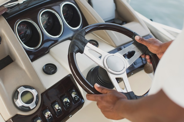 Yacht's captain holds the wheel with his hands