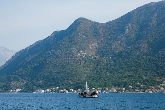 A yacht sailing along the coast of the city of perast on a sunny day.