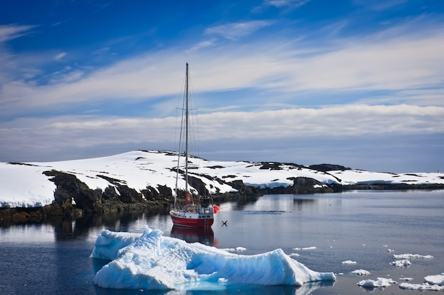 Yacht sailing among the glaciers in antarctica