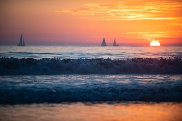 日没時に外洋を航行するヨット。美しい雲と海に沈む夕日。日の出の海の海の景色。