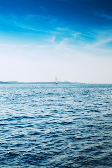 Парусная яхта в синем море парусный корабль на фоне голубого неба и гор