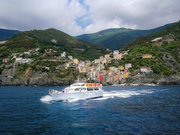 Yacht sailing near the coastal village in riomaggiore, italy
