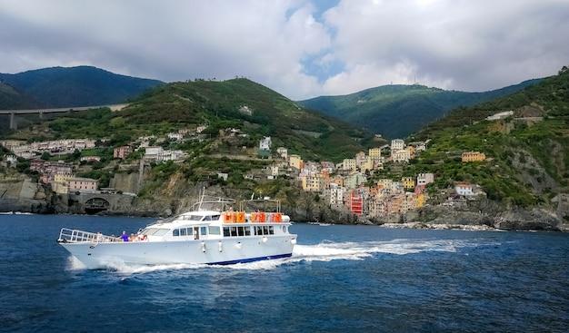イタリア、リオマッジョーレの海岸沿いの村の近くでセーリングヨット