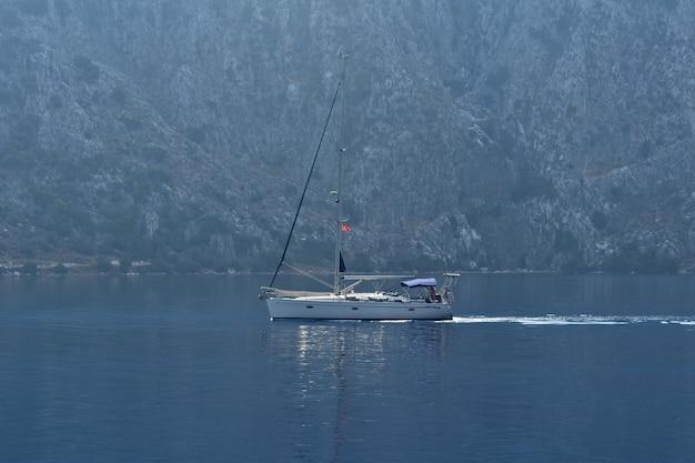 요트는 바위를 따라 바다를 항해한다