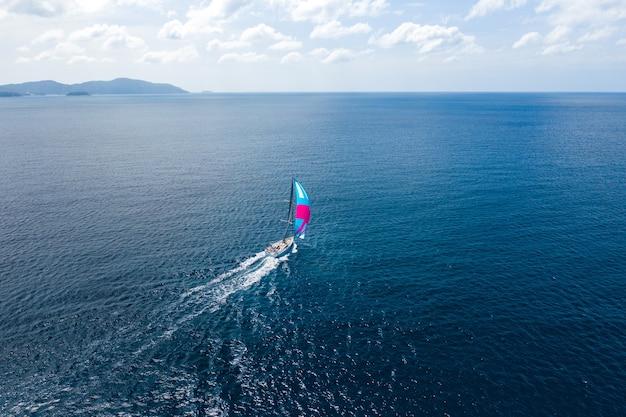 海に色とりどりの帆が付いたヨット