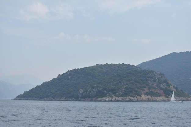 Яхта с белым парусом плывет по морю на фоне гор