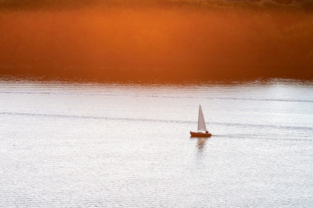 Яхта с белыми парусами в бухте при солнечном свете. планирование яхт в море. красивый водный пейзаж.