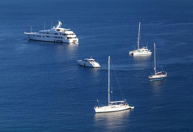 Яхты и лодки в кристально чистой лазурной воде на острове палеокастрица корфу, греция