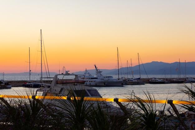 Яхты пришвартовались в морском порту на закате. морской пейзаж с лодками и горами. морская стоянка моторной лодки