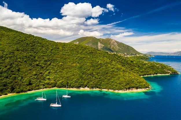 緑の島の近くの湾のヨット。夏休み、ギリシャ、ケファロニア島。