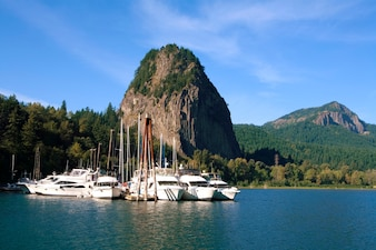 Yachts mooring at dock in remote area with rock formation in background
